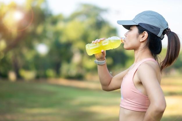 Młoda kobieta fitness picia wody energetycznej podczas rozciągania mięśni w parku na świeżym powietrzu, azjatycki sportowiec, bieganie i ćwiczenia w godzinach porannych. koncepcja sportu i odnowy biologicznej