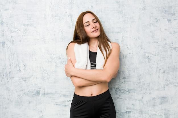 Młoda kobieta fitness przytula, uśmiechając się beztroski i szczęśliwy.