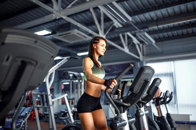Młoda kobieta fitness robi ćwiczenia cardio na siłowni działa na bieżni