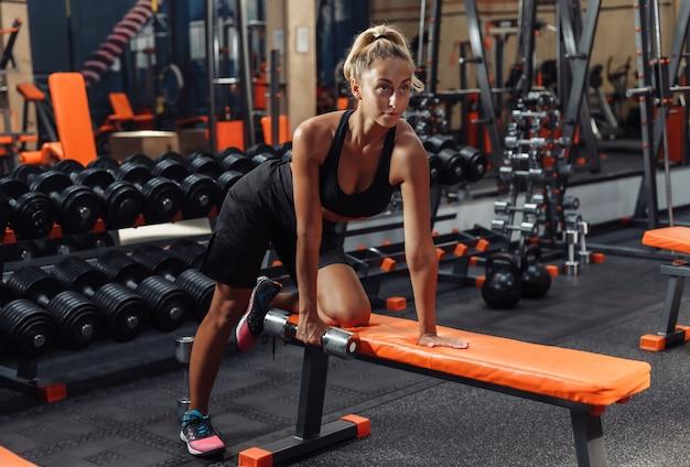 Młoda kobieta fitness robi hantle trakcji jedną ręką przechyloną z ławki na siłowni. koncepcja treningowa z wolnymi ciężarami.
