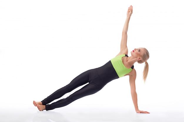 Młoda kobieta fitness szalowanie na podłodze na białym tle
