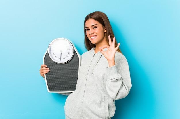 Młoda kobieta fitness trzyma skalę wesoły i pewny siebie, pokazując gest ok.