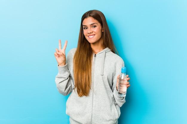 Młoda kobieta fitness trzymając butelkę wody pokazuje numer dwa palcami.
