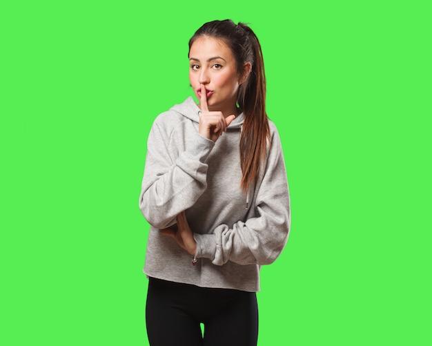 Młoda kobieta fitness utrzymująca sekret lub prosząca o ciszę