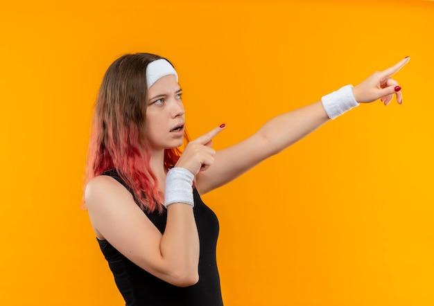 Młoda kobieta fitness w odzieży sportowej patrząc na bok zaskoczony, wskazując palcami obu rąk na coś stojącego na pomarańczowej ścianie
