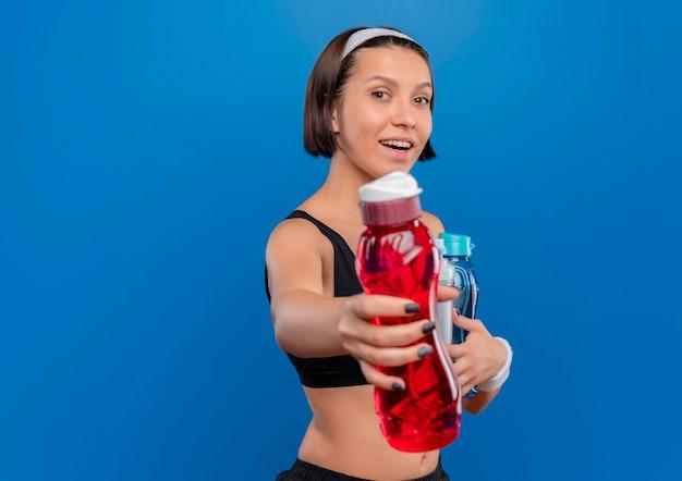 Młoda kobieta fitness w odzieży sportowej trzymając butelki wody z uśmiechem na twarzy, oferując butelkę stojącą nad niebieską ścianą