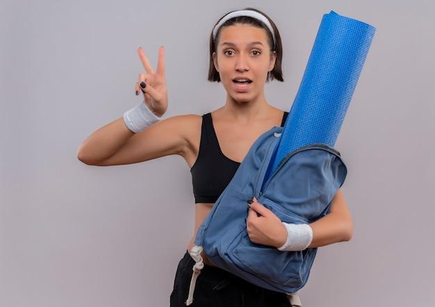 Młoda kobieta fitness w odzieży sportowej trzymając plecak z matą do jogi, uśmiechając się wesoło, pokazując znak zwycięstwa stojący na białej ścianie