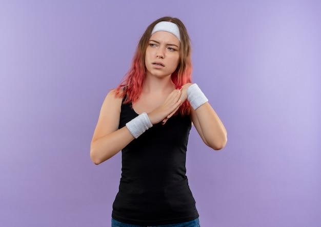 Młoda kobieta fitness w odzieży sportowej, trzymając się za ręce razem robi rozgrzewkę patrząc na bok z poważną twarzą stojącą nad fioletową ścianą