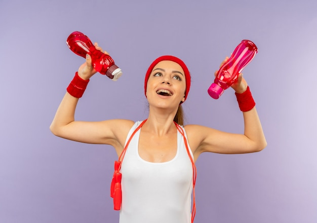 Młoda kobieta fitness w odzieży sportowej z opaską i skakanką na szyi trzymająca butelki wody patrząc w górę szczęśliwa i wesoła stojąca nad szarą ścianą