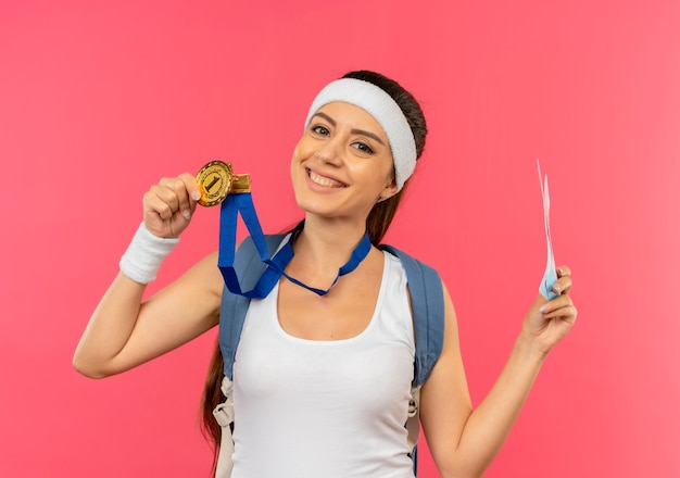 Młoda kobieta fitness w odzieży sportowej z opaską i złotym medalem na szyi z plecakiem trzymającym bilety lotnicze uśmiechnięta wesoło stojąc nad różową ścianą