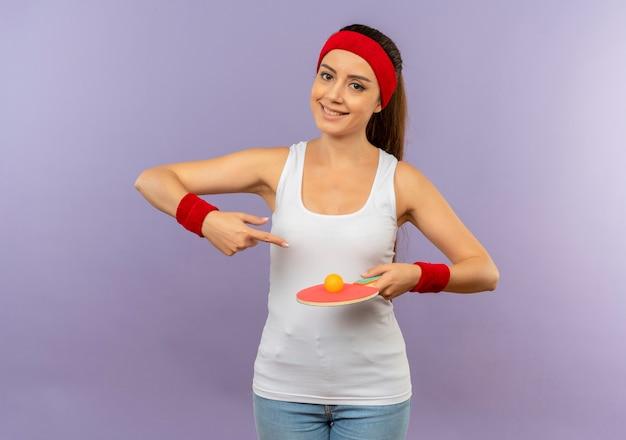 Młoda kobieta fitness w odzieży sportowej z opaską na głowę trzymająca rakietę i piłkę do tenisa stołowego wskazująca palcem wskazującym na rakietę z uśmiechem na twarzy stojącej nad szarą ścianą