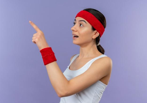 Młoda kobieta fitness w odzieży sportowej z opaską, patrząc na bok zaskoczony i zdumiony, wskazując palcem w bok, stojącego nad fioletową ścianą
