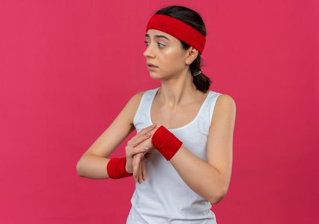 Młoda kobieta fitness w odzieży sportowej z opaską, patrząc na bok zmartwiony rozgrzewką stojącą nad różową ścianą
