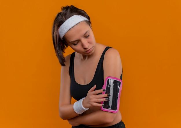 Młoda kobieta fitness w odzieży sportowej z pałąkiem na głowę dotykając jej opaskę smartfona stojąc na pomarańczowej ścianie