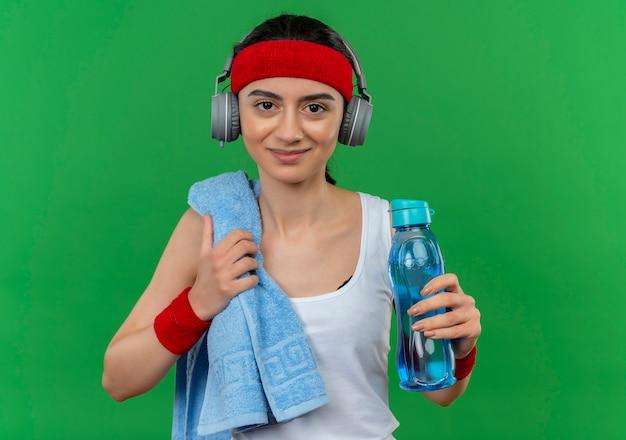 Młoda kobieta fitness w odzieży sportowej z pałąkiem na głowę i ręcznikiem na ramieniu, trzymając butelkę wody uśmiechnięty pewnie stojący nad zieloną ścianą