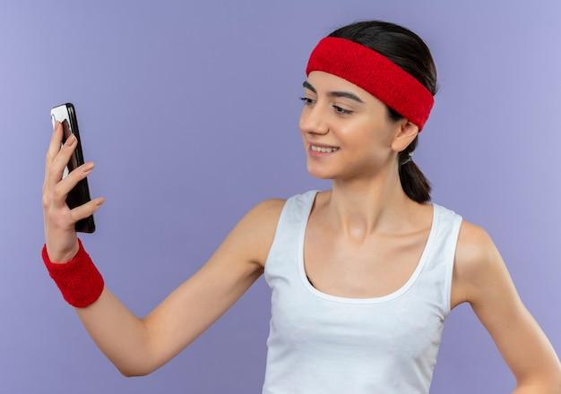 Młoda kobieta fitness w odzieży sportowej z pałąkiem na głowę, patrząc na ekran swojego smartfona, uśmiechając się pewnie stojąc na fioletowej ścianie