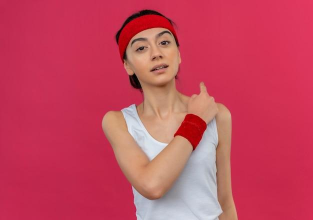 Młoda kobieta fitness w odzieży sportowej z pałąkiem na głowę, patrząc pewnie wskazując wstecz stojąc na różowej ścianie