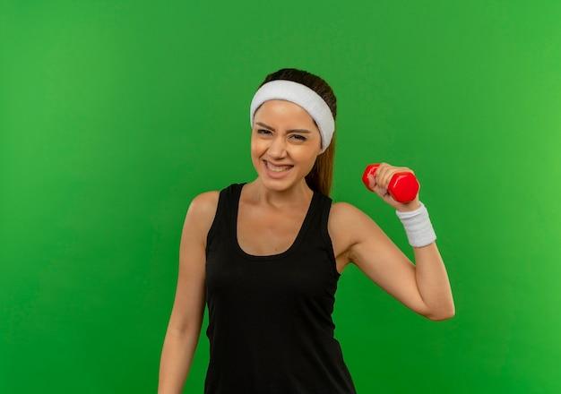 Młoda kobieta fitness w odzieży sportowej z pałąkiem na głowę podnosząc rękę trzymając hantle, uśmiechając się radośnie stojąc na zielonej ścianie