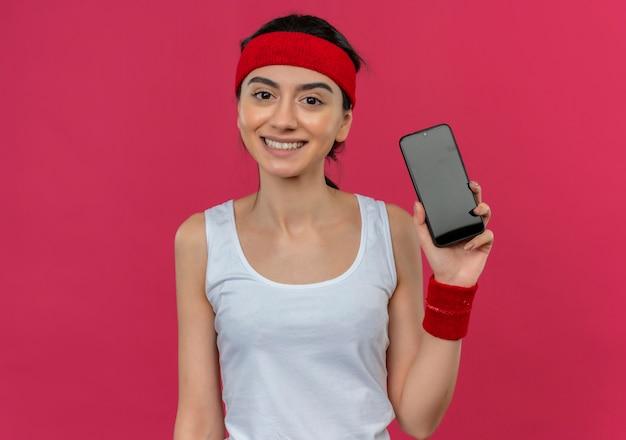 Młoda kobieta fitness w odzieży sportowej z pałąkiem na głowę pokazuje smartphone szczęśliwy i pozytywny uśmiechnięty wesoło stojąc na różowej ścianie