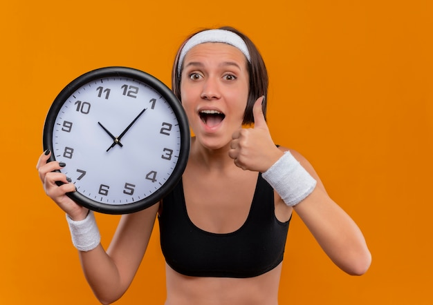 Młoda kobieta fitness w odzieży sportowej z pałąkiem na głowę trzyma zegar ścienny szczęśliwy i podekscytowany, pokazując kciuk do góry stojąc nad pomarańczową ścianą
