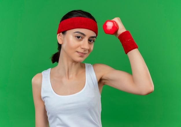 Młoda kobieta fitness w odzieży sportowej z pałąkiem na głowę, trzymając hantle, podnosząc rękę, uśmiechając się pewnie stojąc na zielonej ścianie