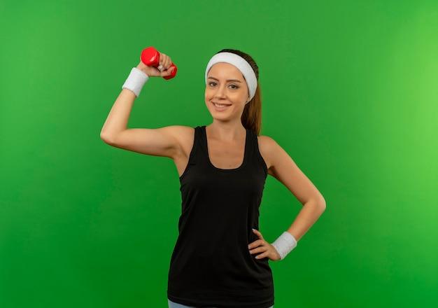 Młoda kobieta fitness w odzieży sportowej z pałąkiem na głowę, trzymając hantle, robi ćwiczenia patrząc pewnie z uśmiechem na twarzy stojącej na zielonej ścianie