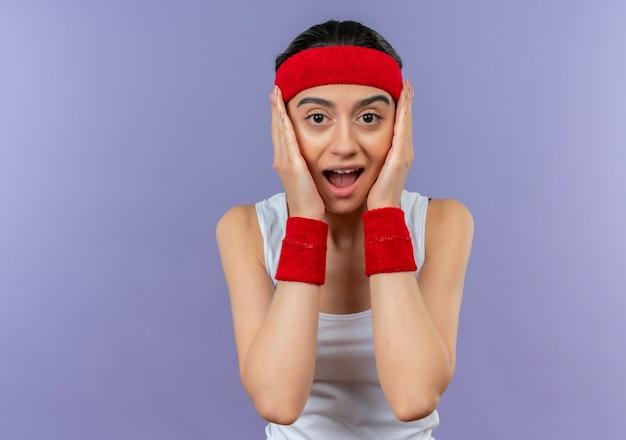 Młoda kobieta fitness w odzieży sportowej z pałąkiem na głowę wstrząśnięty rękami na twarzy stojącej nad fioletową ścianą