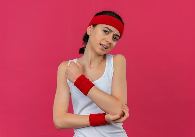 Młoda kobieta fitness w odzieży sportowej z pałąkiem na głowę źle patrzy dotykając jej łokcia o bólu stojącego nad różową ścianą
