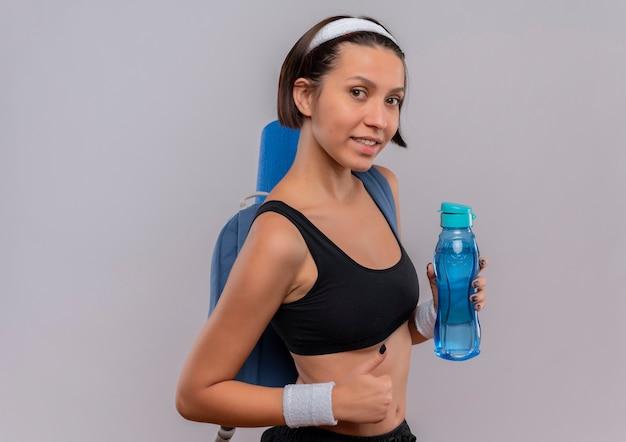 Młoda kobieta fitness w odzieży sportowej z plecakiem i matą do jogi, trzymając butelkę wody uśmiechnięty, pokazując kciuk do góry stojąc na białej ścianie