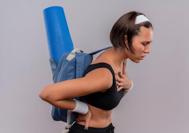 Młoda kobieta fitness w odzieży sportowej z plecakiem i matą do jogi źle patrząc trzymając rękę na jej klatce piersiowej zmęczony stojąc na białej ścianie