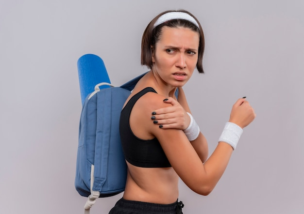 Młoda kobieta fitness w odzieży sportowej z plecakiem i matą do jogi źle wyglądający dotykając jej ramienia uczucie bólu stojącego na białej ścianie