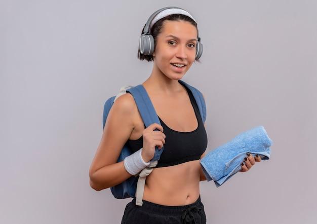 Młoda kobieta fitness w odzieży sportowej z plecakiem i słuchawkami na głowie, trzymając ręcznik, uśmiechając się pozytywnie i szczęśliwie stojąc na białej ścianie