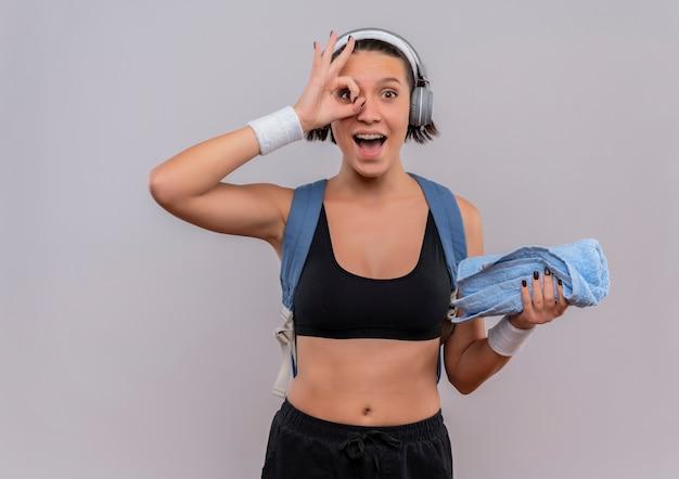 Młoda kobieta fitness w odzieży sportowej z plecakiem i słuchawkami na głowie trzymając ręcznik, uśmiechając się radośnie