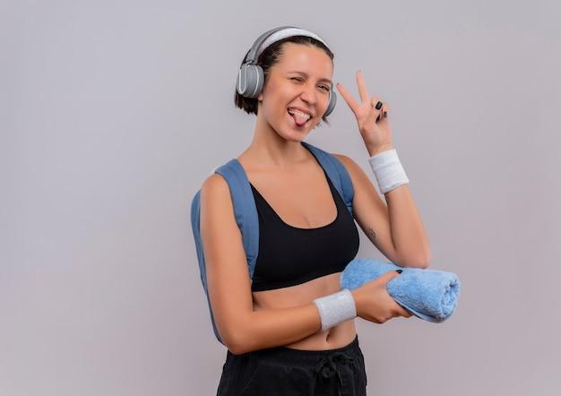 Młoda kobieta fitness w odzieży sportowej z plecakiem i słuchawkami na głowie trzymając ręcznik wystający język uśmiechnięty pokazując znak zwycięstwa stojący nad białą ścianą