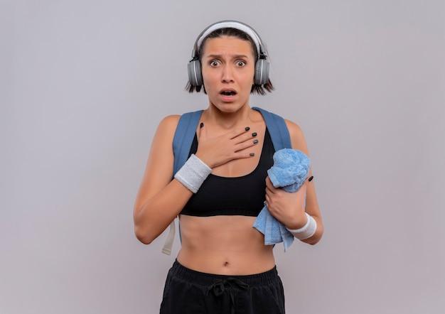 Młoda kobieta fitness w odzieży sportowej z plecakiem i słuchawkami na głowie trzymając ręcznik z ręką na piersi przestraszony stojąc nad białą ścianą