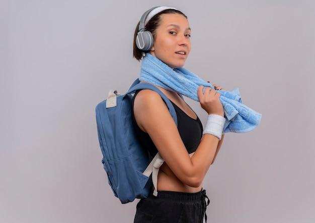 Młoda kobieta fitness w odzieży sportowej z plecakiem i słuchawkami na głowie z ręcznikiem na szyi, patrząc pewnie uśmiechnięty stojący nad białą ścianą