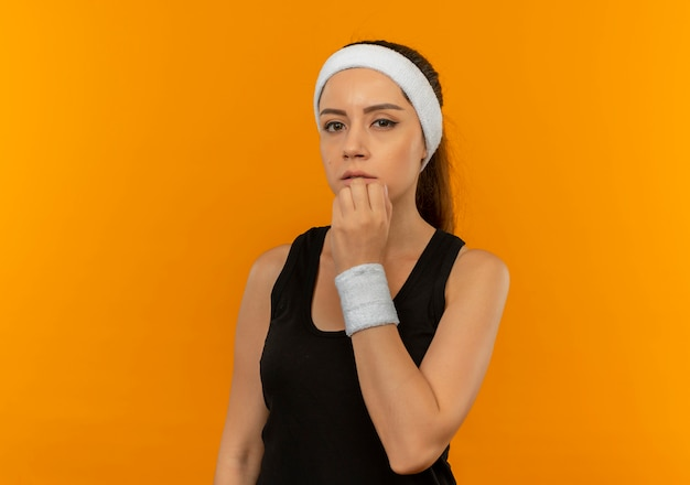 Młoda kobieta fitness w odzieży sportowej zdziwiony stojąc na pomarańczowej ścianie