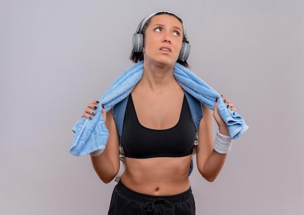 Młoda kobieta fitness w odzieży sportowej ze słuchawkami na głowie i ręcznikiem na szyi, patrząc na bok zmęczony i znudzony stojący nad białą ścianą