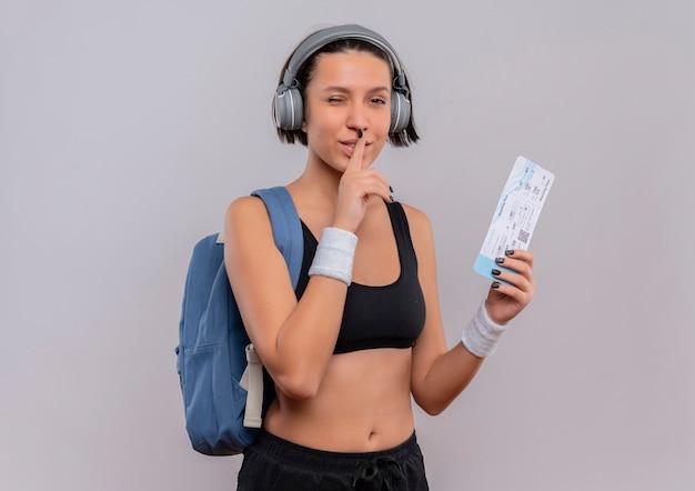 Młoda kobieta fitness w odzieży sportowej ze słuchawkami na głowie z plecakiem trzymając bilet lotniczy, czyniąc gest ciszy z palcem na ustach