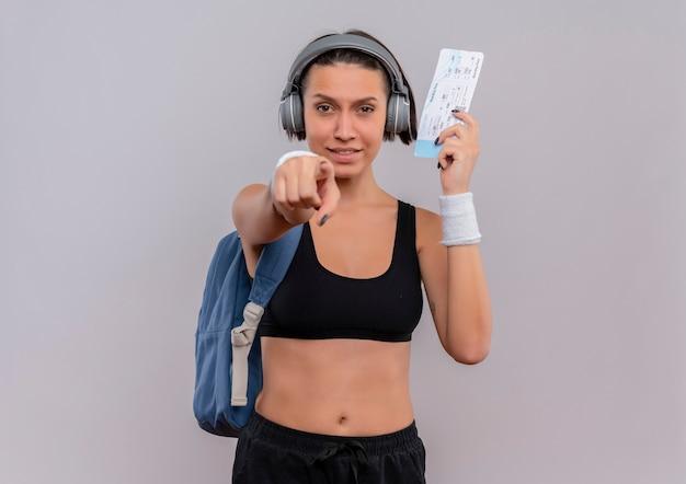 Młoda kobieta fitness w odzieży sportowej ze słuchawkami na głowie z plecakiem trzymając bilet lotniczy, wskazując palcem na aparat uśmiechnięty stojący nad białą ścianą
