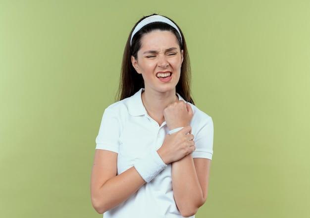 Młoda kobieta fitness w opasce dotykając jej nadgarstka, patrząc zły ból stojąc na jasnym tle