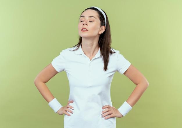 Młoda kobieta fitness w opasce patrząc na bok z pewnym siebie wyrazem ramionami na biodrze, stojąc na jasnym tle
