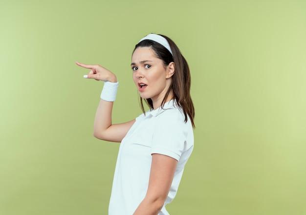 Młoda kobieta fitness w opasce patrząc zdezorientowany, wskazując palcem na bok, stojąc na jasnym tle