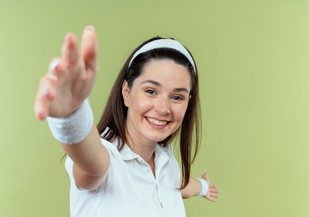 Młoda kobieta fitness w opasce szczęśliwy i pozytywny, czyniąc powitalny gest rękami stojącymi nad jasną ścianą
