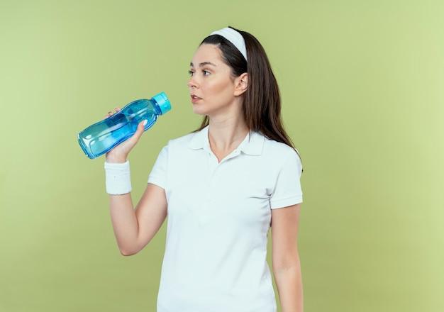 Młoda kobieta fitness w opasce trzyma butelkę wody patrząc na bok z pewną miną stojącą nad jasną ścianą