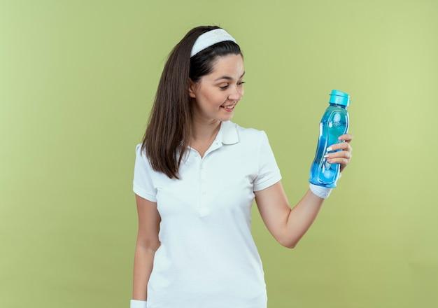 Młoda kobieta fitness w opasce trzyma butelkę wody patrząc na to uśmiechnięty z szczęśliwą twarzą stojącą na jasnym tle