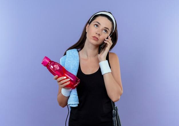 Młoda kobieta fitness w opasce trzyma butelkę wody rozmawia przez telefon komórkowy patrząc na bok zdziwiony stojąc na niebieskim tle