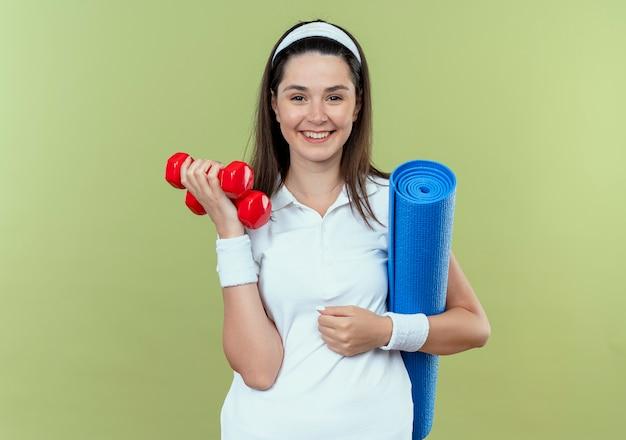 Młoda kobieta fitness w opasce trzyma dwa hantle i matę do jogi patrząc na kamery uśmiechnięty stojący na jasnym tle
