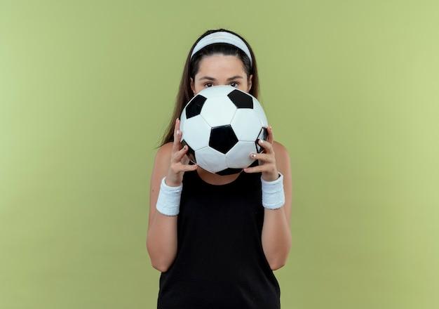 Młoda kobieta fitness w opasce trzyma piłkę nożną, ukrywając twarz za piłką, zerkając nad stojącą na jasnym tle