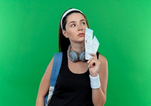 Młoda kobieta fitness w opasce z plecakiem trzymając bilety lotnicze patrząc na bok z poważną twarzą stojącą na zielonym tle